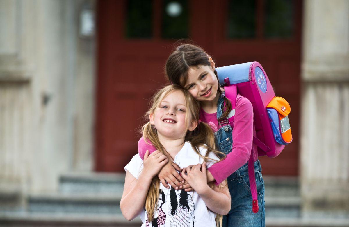 Zwei kleine Schulmädchen mit Tornister auf dem Rücken umarmen sich freundschaftlich.