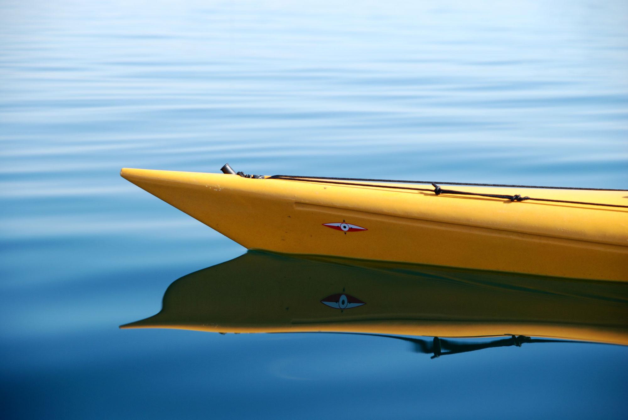 Man sieht die Spitze eines gelben Kanus auf dem Wasser.